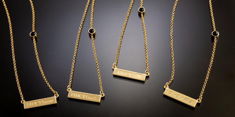 Gold pendants and chains on a gray to black background