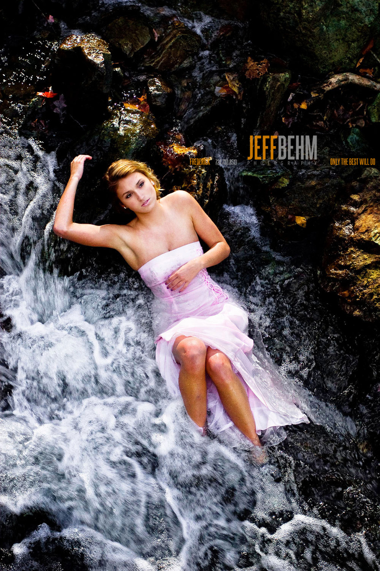 Model wearing pink dress lying in stream